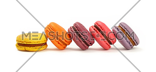Row of several fresh colorful traditional French macaroon pastry cookies (macarons, macaroni) isolated on white background, close up, low angle view