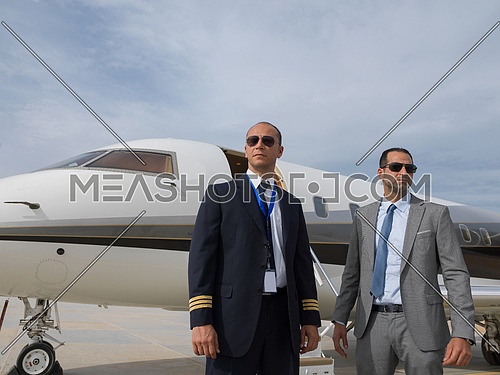 portrait of middle eastern pilot and a successful businessman in front of private airplane