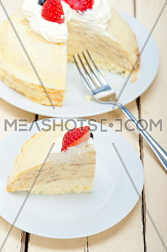 crepe pancake cake with whipped cream and strawberry on top
