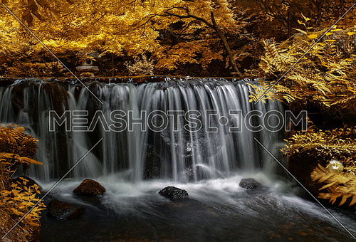 Beautiful river waterfall in autumn forest, a small waterfall in mountain