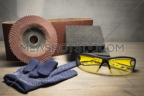 Various grinding tools - sanding belt, abrasive sponge and flap disc for angle grinder, safety gloves and goggles, renovation, safety and health at work concept