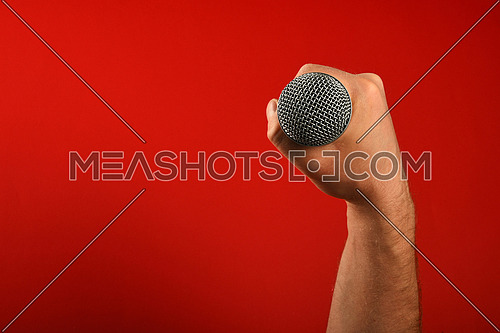 Man hand holding voice microphone in fist over red background, top view, point of view