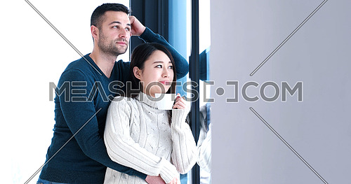 young multiethnic romantic couple enjoying morning coffee by the window in their luxury home