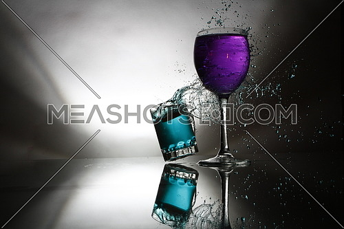 2 glasses with colored liquid smash into each other