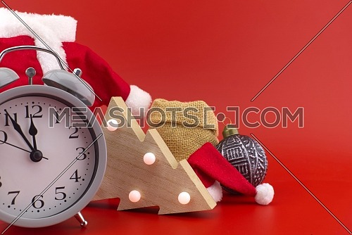 New Year and Christmas scene on festive red background with with vintage alarm-clock, miniature santa costume and gift in sack bag, copy space for text