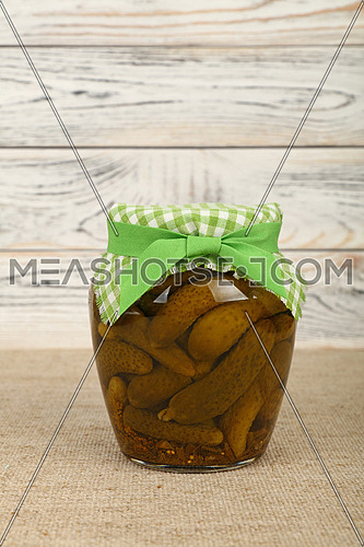 Close up of one glass jar of pickled small gherkin cucumbers checkered linen textile fabric lid decoration and green ribbon on canvas over white wooden background, low angle side view