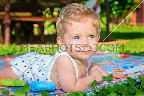 Beautiful baby boy eight month old crawling in the garden,close up.