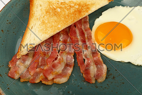 Close up English breakfast, sunny side egg, toasted bread and roasted bacon slices on blue plate, high angle view