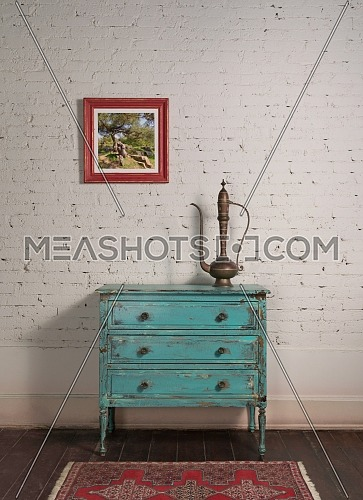 White brick wall with copper antique tea pot on the top of shabby chic vintage turquoise cabinet and hanged painting in living room