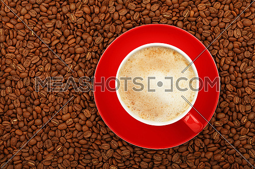 Full latte cappuccino with milk froth in big red cup with saucer on background of roasted coffee beans, elevated top view, close up
