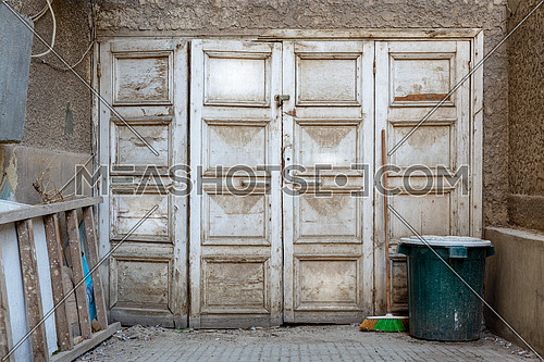 Wooden grunge weathered abandoned door painted in white, green trash can and ladder