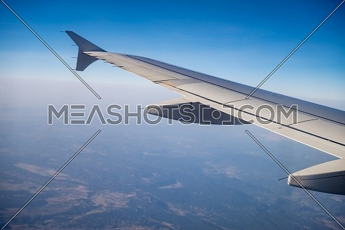Ariel Shot through the aircraft window during the flight. Aircraft wing over blue skies and Pyrenees mountains.