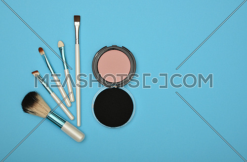 Close up set of face makeup blush, beige sponge and brushes over blue background, elevated top view, directly above