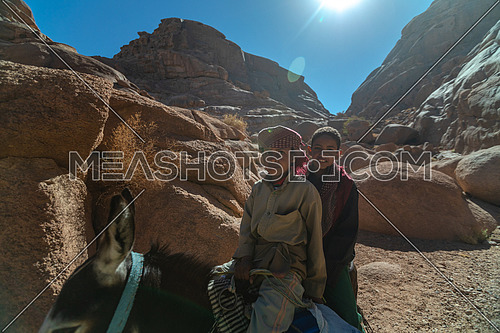 Bedouin children riding a donky at SInai Mountain at day