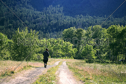A girl walking on a path towards a forest