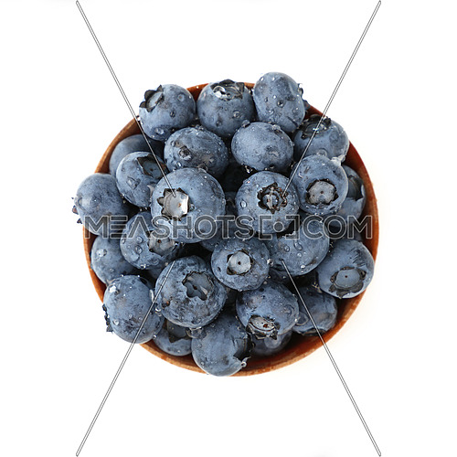 Portion of fresh washed blueberry berries in rustic wooden bowl, wet with water drops, isolated on white background, close up, elevated top view, directly above