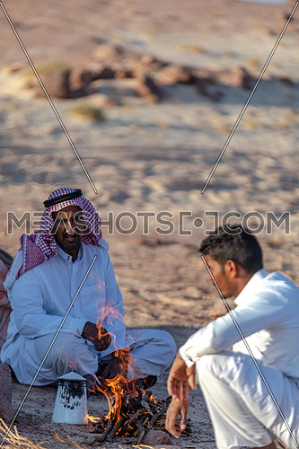 Two Bedouin Males wearing traditional clothing, sitting and making tea at Ain Hodouda area in Sinai at day.