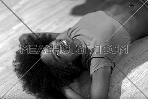 happy african american woman with a curly afro hairstyle in a  gym relaxing after pilates workout