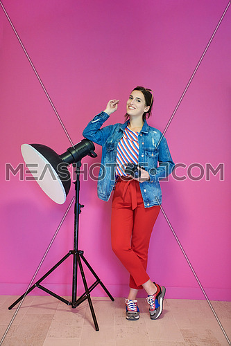 Young woman leaning against studio flashlight and holding camera over a pink background. Female photographer wearing fashionable and casual clothes  posing in the studio. Professional photography equipment