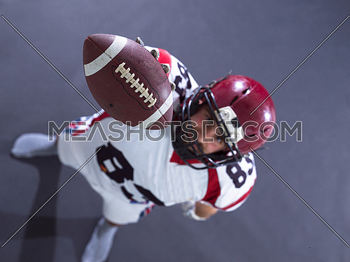 Portrait of american football player showing football to camera against gray background