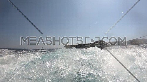 Low angel shot for Sea water moving fast of boat motor showing Inflatable boat at day