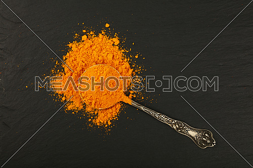 Close up one vintage antique metal spoon full of yellow turmeric powder spice on background of black slate board, elevated top view, directly above