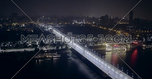 Aerial shot flying over the river Nile and 15 of May Bridge at night