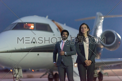 young successful middle eastern businessmen walking in front of private airplane