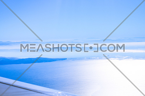 top view from a plane showing clear beautiful blue sky and the ocean underneath along side with an ending of a mountain