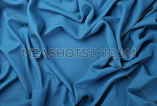Close up abstract textile background of heart shaped blue folded pleats of fabric, elevated top view, directly above