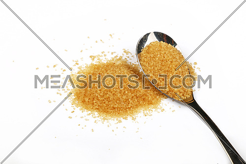 Metal spoon full of brown cane sugar with pinch of sugar spilled around isolated on white background, close up, high angle view