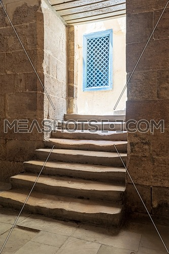 Aged narrow dark vaulted passage and staircase leading to outdoor small lobby with blue wooden windows at Ottoman era historic Soliman Agha El Silahdar, complex building, Medieval Cairo, Egypt