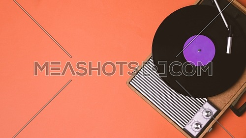 Retro vinyl player and turnable on a orange background. Entertainment 70s. Listen to music. Top view.