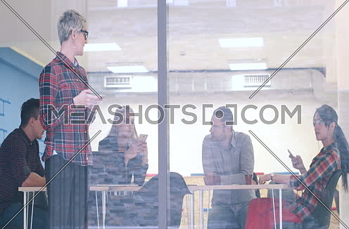 Business Woman Looking Through A Window And using On A Cell Phone during bussines meeting