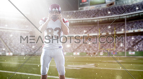 American Football Player isolated on big modern stadium field with lights and flares