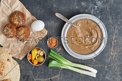 egyptian traditional breakfast foul, falafel and eggs on a wooden table top