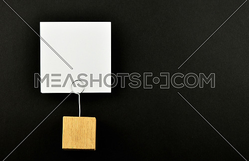 One white paper note with wooden holder isolated at black paper background for presentation