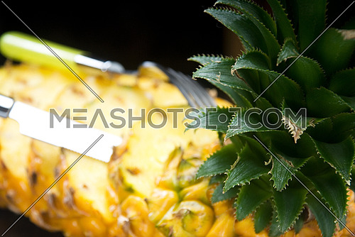 ripe vibrant pineapple sliced on a black plate with knife and fork