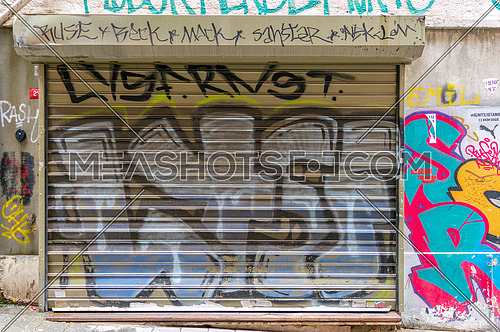 Istanbul, Turkey - April 18, 2017: Closed shop exterior with metal rolling door covered with colorful graffiti near Istiklal Street