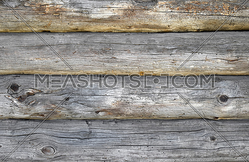 Old antique unpainted wooden vintage cracked pale logs wall of blockhouse, texture background