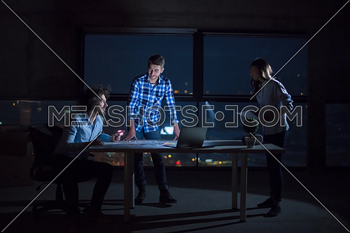 young team of business people in group, architect and engineer on construction site checking documents and business workflow using laptop computer in new startup office at night