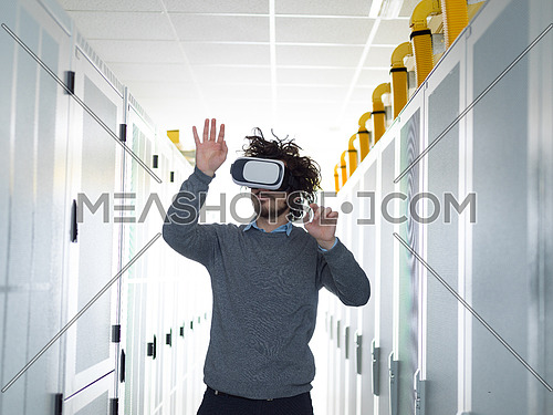 young IT engeneer using virtual reality headset over server room background