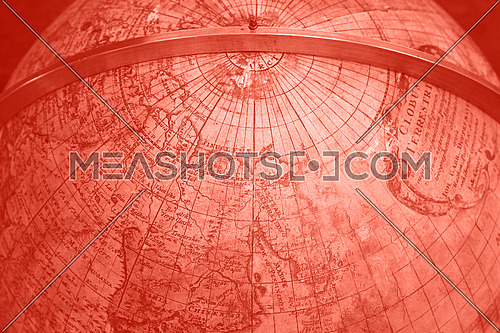 Close up coral pink toned background of old antique vintage earth globe map, high angle view