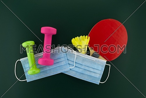 Dumbbells, shuttlecock, table tennis racket covered with a protective surgical face mask. Activity during the quarantine period concept with free copy space