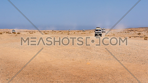 Egypt, Black Desert. Moving off-road vehicle with a panoramic view on the stone desert . Tracks on the sand from the automotive rubber.