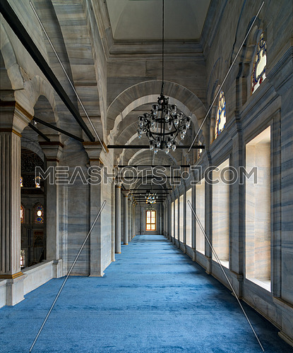 Passage in Nuruosmaniye Mosque, a public Ottoman Baroque style mosque, with columns, arches and floor covered with blue carpet lighted by side windows located in Shemberlitash, Fatih, Istanbul, Turkey