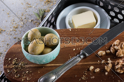 A bowl filled with green Olives and and butter with a knife moist with butter and walnuts and rosemary leaves