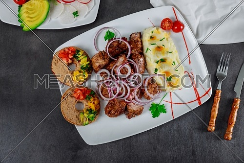 Roasted grilled skewers pork meat with mashed potatoes in white plate on table