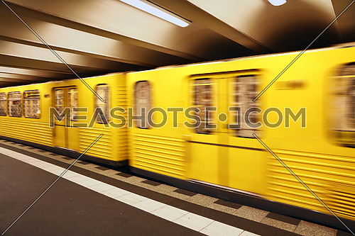 Close up yellow metro underground train carriage in motion, diagonal angle view