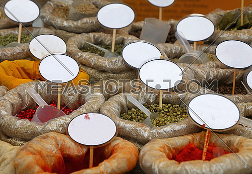 Close up many canvas bags of assorted spices, yellow turmeric, red paprika and green peppercorns, with copy space of blank price tags on retail display of market stall, high angle view